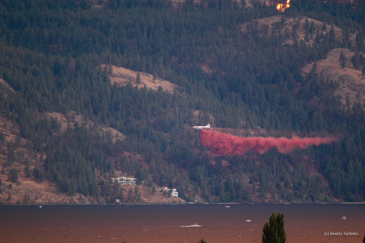 August 18th, 2003 - 17:54 PST The fire slowly moves toward the first homes. Here, a DC-6 drops another line of retardant.